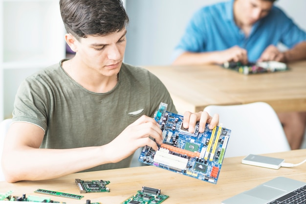 Young student learning to assemble motherboard Free Photo