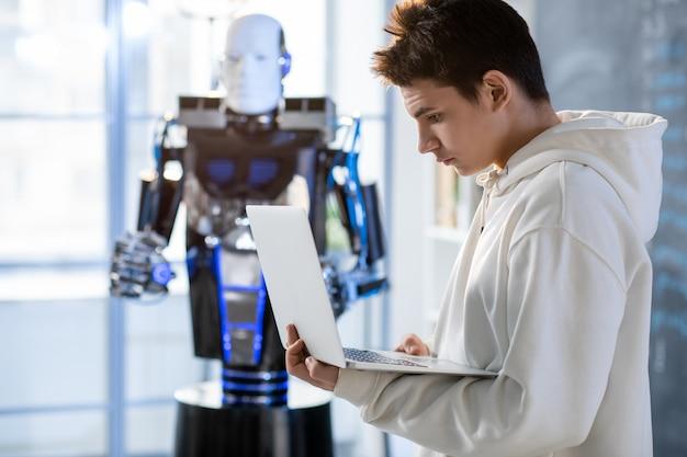 現代の研究所の研究室や教室で自動化ロボットを操作しながらノートパソコンのディスプレイを見ている若い学生 Premium写真