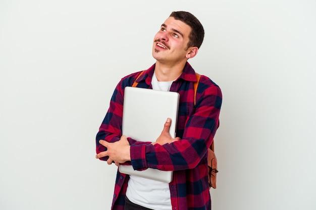 목표와 목적을 달성하는 꿈을 꾸고 흰 벽에 고립 된 노트북을 들고 젊은 학생 남자 프리미엄 사진