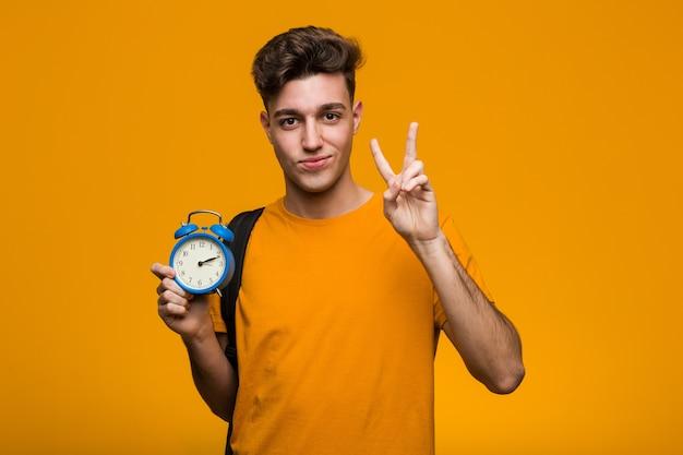 いくつかの素晴らしいアイデア、創造性の概念を持つ目覚まし時計を保持している若い学生男。 Premium写真