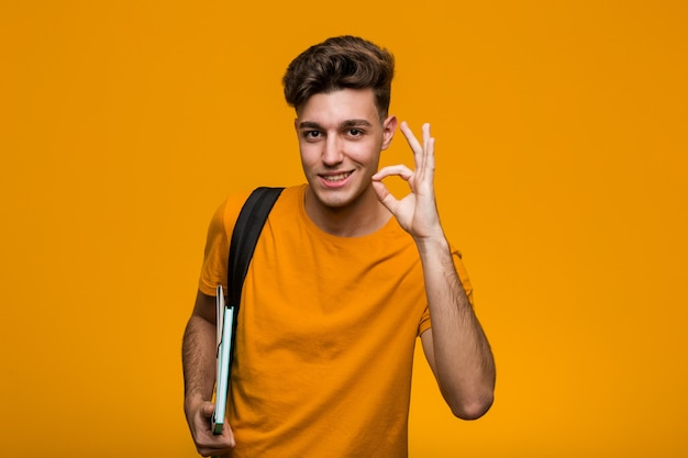 本を持って若い学生男は、広く笑って、自分自身を指して驚いた。 Premium写真
