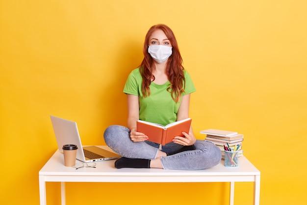 Giovane studente in maschera medica che studia a casa durante la quarantena, annoiato dell'apprendimento a distanza, seduto con le gambe incrociate sul tavolo bianco con il libro in mano. Foto Gratuite