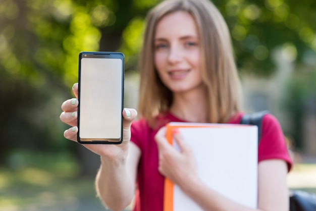 Young student showing smartphone template Free Photo