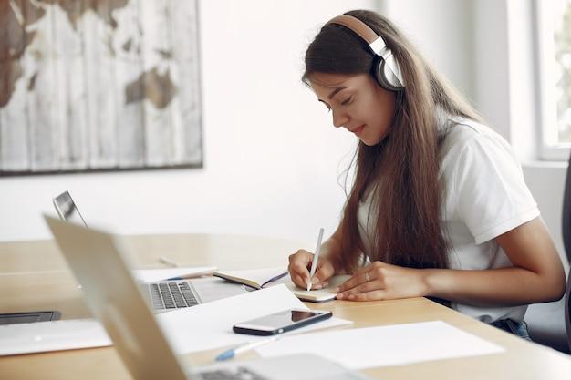 테이블에 앉아 노트북을 사용하는 젊은 학생 무료 사진