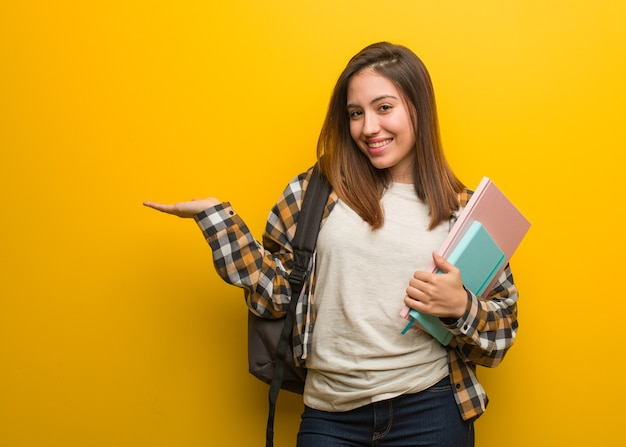 Young student woman holding something with hand Premium Photo