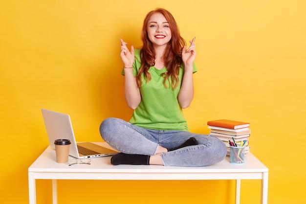 Молодая женщина-студент на рабочем месте с ноутбуком и книгами, сидя со скрещенными пальцами, желает всего наилучшего, сидя со скрещенными ногами на белом столе, улыбается прямо в камеру. Бесплатные Фотографии