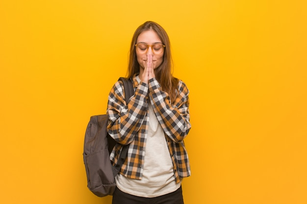 Young student woman praying very happy and confident Premium Photo