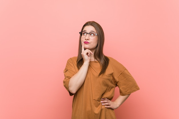 Young student woman wearing eyeglasses looking sideways with doubtful and skeptical expression. Premium Photo