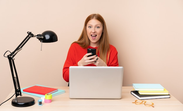 Young student woman in a workplace with a laptop surprised and sending a message Premium Photo