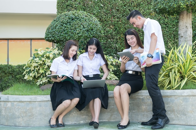 Young students play computer and reading book in university, lifestyle learning Premium Photo