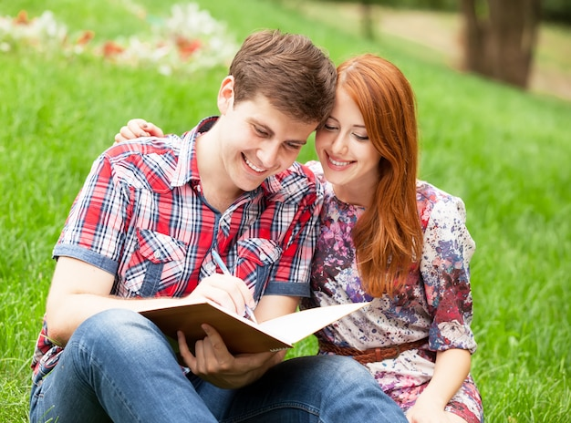 Young students sitting on green grass with note book. Premium Photo