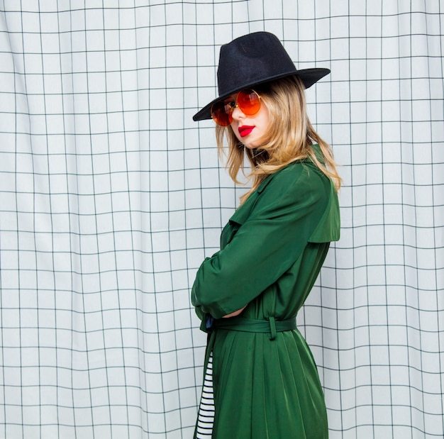 Young style woman in sunglasses and green cloak in 90s style Premium Photo
