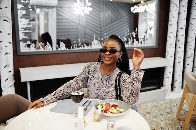 세련 된 젊은 아프리카 계 미국인 여자, 검은 색 선글라스를 착용하고 레스토랑에 앉아 와인과 함께 건강식을 즐기십시오. 프리미엄 사진