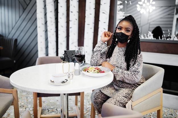 젊은 세련 된 아프리카 계 미국인 여자, 검은 얼굴 마스크를 쓰고 레스토랑에 앉아 와인과 함께 건강 한 음식을 즐기고. 프리미엄 사진
