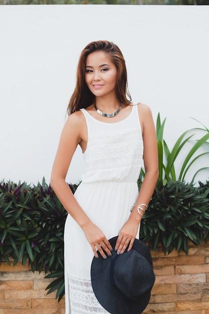 Giovane donna asiatica alla moda in abito bianco boho, stile vintage, naturale, sorridente, felice, vacanza tropicale, hotel, luna di miele Foto Gratuite
