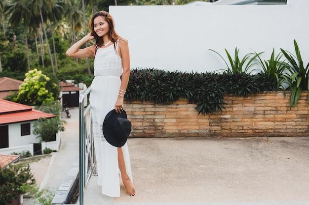 Giovane donna asiatica alla moda in abito bianco boho, stile vintage, naturale, sorridente, felice, vacanza tropicale, hotel, sfondo di palme Foto Gratuite
