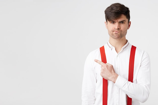 Young stylish attractive guy in white shirt and red suspender pointing with index finger to the left side with unsatisfied displeased facial expression Free Photo
