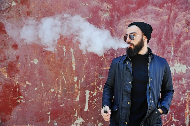 Young stylish bearded man in a black hat with an electronic cigarette or vape Premium Photo