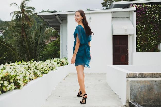 Giovane bella donna alla moda in vestito blu, tendenza della moda estiva, vacanze, giardino, terrazza dell'hotel tropicale, sorridente, camminando Foto Gratuite