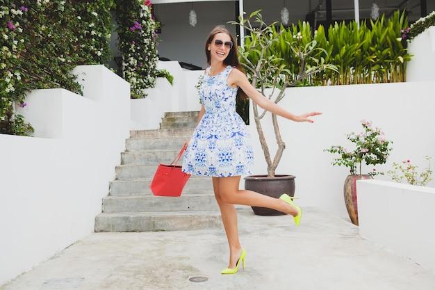 Молодая стильная красивая женщина в синем платье с принтом, красной сумке, солнцезащитных очках, счастливом настроении, модном наряде, модной одежде, улыбается, лето, аксессуары, игривая, гуляет, работает на высоких каблуках желтых туфлях Бесплатные Фотографии