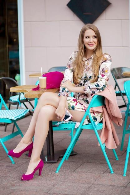 街のカフェに座っている若いスタイリッシュな美しい女性 無料写真