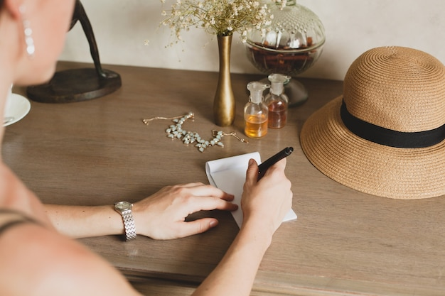 Young stylish beautiful woman sitting at table in resort hotel room, writing a letter, holding pen, straw hat, vintage style, hands close-up, details, accessories, travel diary Free Photo