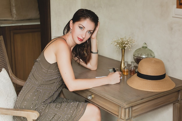 Young stylish beautiful woman sitting at table in resort hotel room, writing a letter, thinking, sophisticated, smiling, happy, bohemian outfit, holding pen, straw hat, vintage style Free Photo