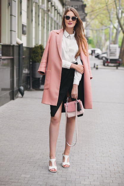 通りを歩いて、ピンクのコートを着ている若いスタイリッシュな美しい女性 無料写真