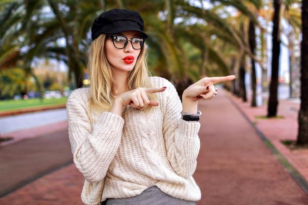 彼女の指で方向を示すスタイリッシュな金髪の若い女性は、驚いた感情、トレンディでエレガントな魅力的な衣装、手のひらでバルセロナの通り、旅行気分を終了しました。 無料写真