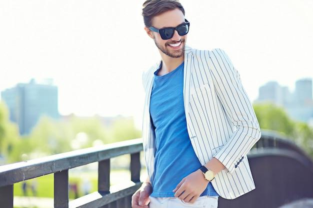 壁近くの通りに立っているスーツヒップスター布ライフスタイルで若いスタイリッシュな自信を持って幸せなハンサムな実業家モデル 無料写真