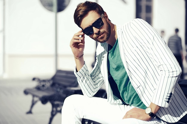 Young stylish confident happy handsome businessman model  in suit cloth lifestyle in the street in sunglasses Free Photo