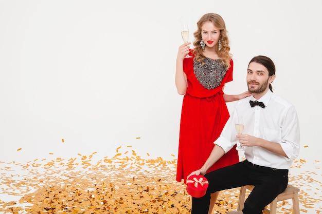 Молодая стильная влюбленная пара держит бокалы и пьет шампанское, празднуя новый год Бесплатные Фотографии