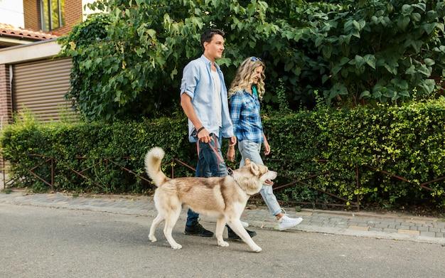 Молодая стильная пара прогулки с собакой на улице. мужчина и женщина счастливы вместе с хаски Бесплатные Фотографии