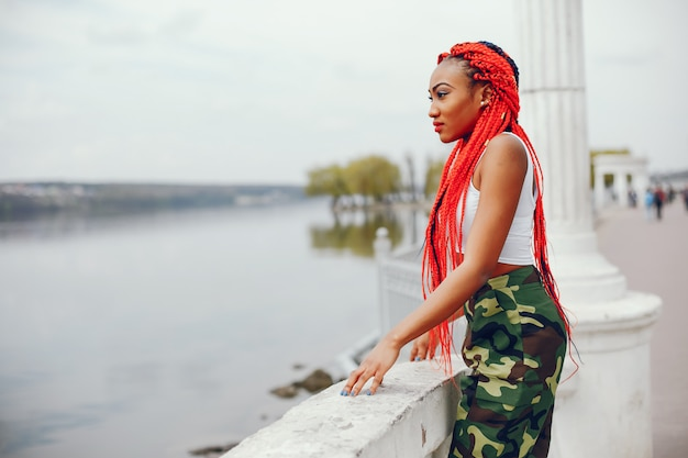 A young and stylish dark-skinned girl with red dreads walking in the summer park near river Free Photo