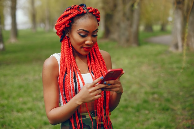 A young and stylish dark-skinned girl with red dreads walking in the summer park with phone Free Photo