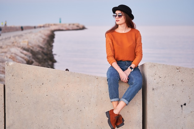 Young stylish girl sitting in a sea port Premium Photo
