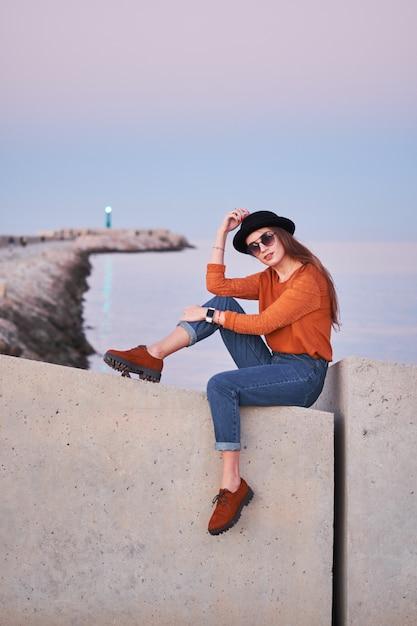 Young stylish girl sitting at a sea port Premium Photo