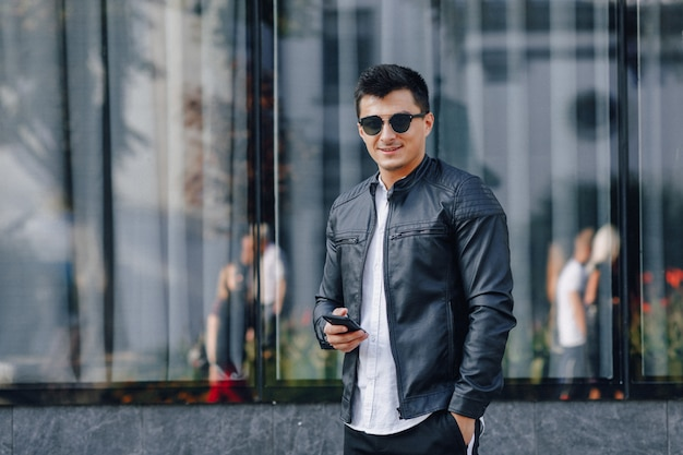 Young stylish guy in glasses in black leather jacket with phone on glass background Free Photo