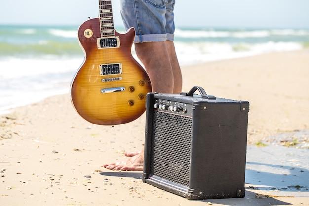 楽器、音楽とリラクゼーションの概念とビーチでスタイリッシュな若者 無料写真
