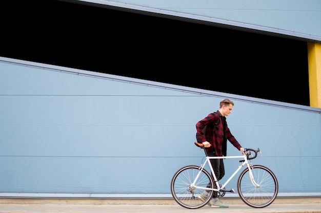 Young stylish guy walks with a white bicycle in front of a blue wall Premium Photo