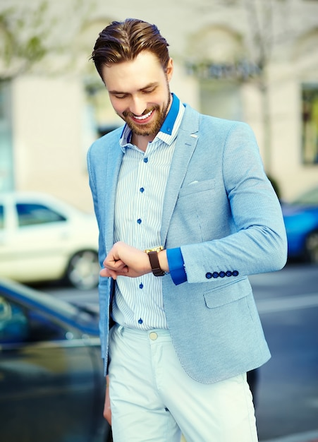 Young stylish handsome man in suit in the street look his watch Free Photo