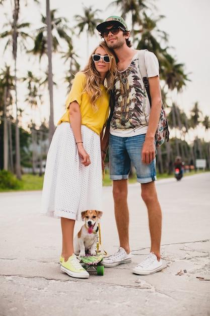 Молодая стильная хипстерская влюбленная пара на отдыхе с собакой и скейтбордом, развлекаясь Бесплатные Фотографии
