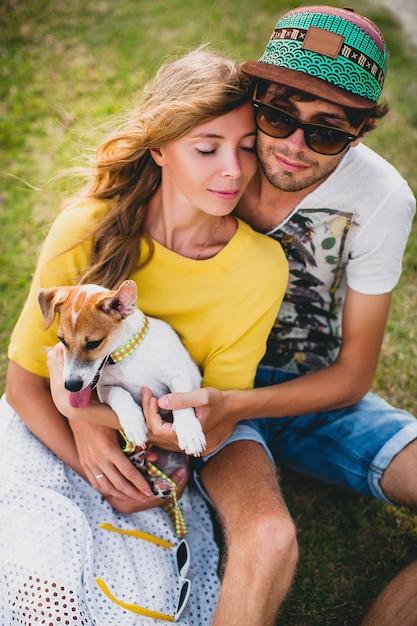 Молодая стильная хипстерская влюбленная пара сидит на траве и играет с собакой на тропическом пляже Бесплатные Фотографии