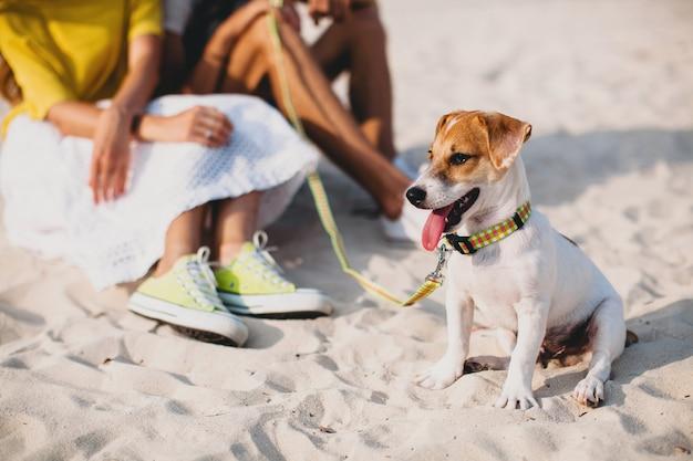 Молодая стильная хипстерская влюбленная пара гуляет и играет с собакой на тропическом пляже Бесплатные Фотографии