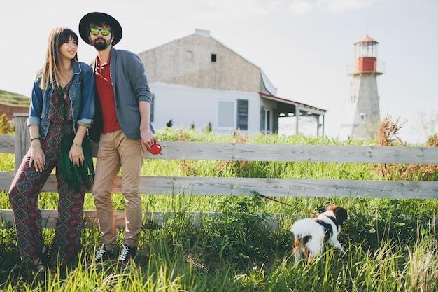 Молодая стильная хипстерская влюбленная пара гуляет с собакой в сельской местности, летняя мода в стиле бохо Бесплатные Фотографии