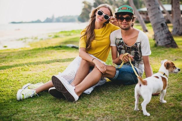 Giovani coppie alla moda hipster nell'amore che si siede sull'erba che gioca con il cane in spiaggia tropicale Foto Gratuite
