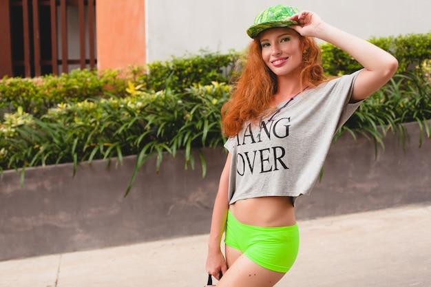 Giovane donna alla moda hipster allo zenzero, camminando in strada, berretto verde, t-shirt oversize grigia, divertirsi, abbigliamento alla moda, vestito di moda, stile adolescente urbano, zaino, viaggiatore Foto Gratuite