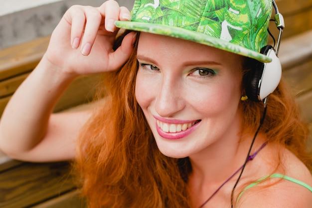 Молодая стильная хипстерская счастливая рыжая женщина, слушающая музыку, наушники, зеленую кепку, улыбается, смешное лицо крупным планом, весело, сумасшедшее настроение, городской стиль Бесплатные Фотографии