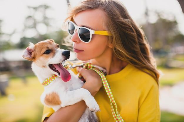 歩くと犬と遊ぶ若いスタイリッシュな流行に敏感な女性 無料写真