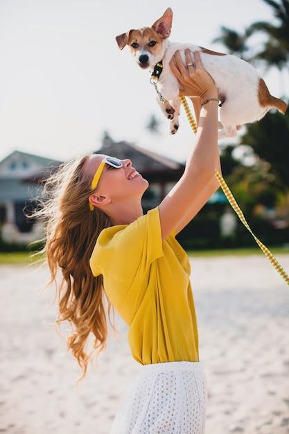 Giovane donna alla moda hipster che tiene camminare giocando cucciolo di cane jack russell, parco tropicale, sorridente e divertirsi, vacanze, occhiali da sole, berretto, camicia gialla, spiaggia di sabbia Foto Gratuite